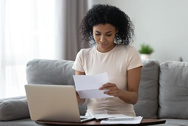 woman looking happy to receive mail infront of her laptop